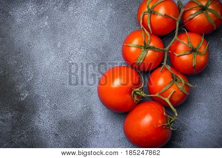 Fresh grape tomatoes on branch for use as cooking ingredients on dark background. Top view, Healthy eating, copy space
