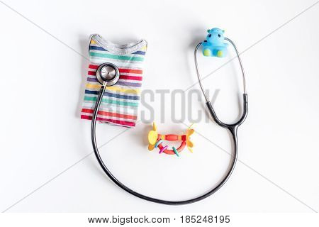 Pediatrician workplace with stethoscope and child clothes on white table background top view