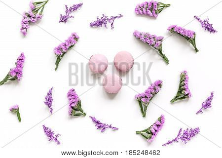 lady morning with macaroons and mauve flowers on white desk background top view pattern