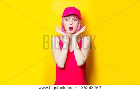 portrait of beautiful surprised young woman in cap on the wonderful yellow studio background