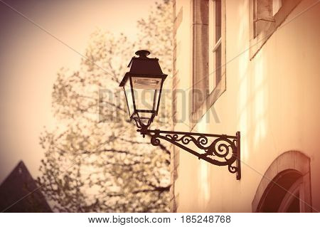 photo of black lantern on the wall of stone beautiful building