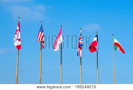 Flags of different countries on the flagpoles on the blue sky. The flags of the USA CanadaUK France Italy and Monaco.