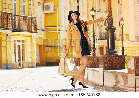 Fashion Shopping. Beautiful And Young Stylish Woman In Hat And Beige Coat Walking In The City With S