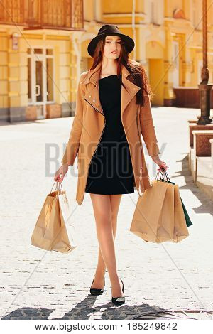 Shopping In The City. Stylish And Beautiful Young Girl In Hat And Beige Coat Walking In The City Wit