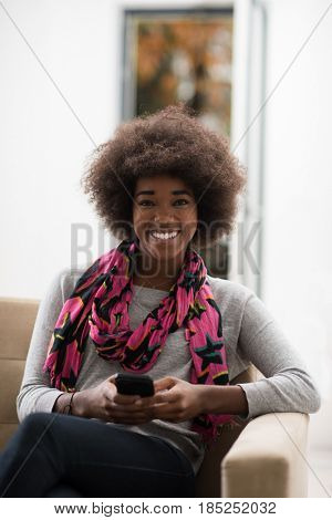 young happy african american woman sitting on sofa and using mobile phone at luxury home