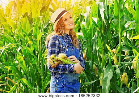 Harvest Time. Portrait Of Beautiful And Young Farmer Girl In Hat And Coveralls Holding Corn In Her H