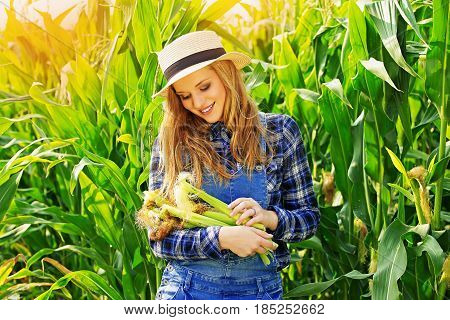 Corn Harvest. Portrait Of Attractive And Young Girl In Hat And Coveralls Holding Corn While Standing