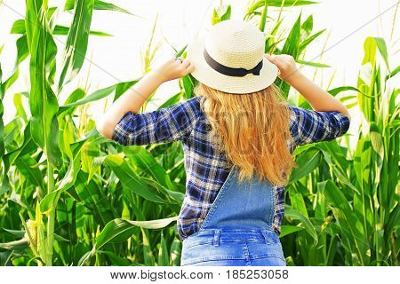 Farmer Beauty. Portrait Of Beautiful Red Haired Girl In Hat And Coveralls Posing With Her Back To Ca
