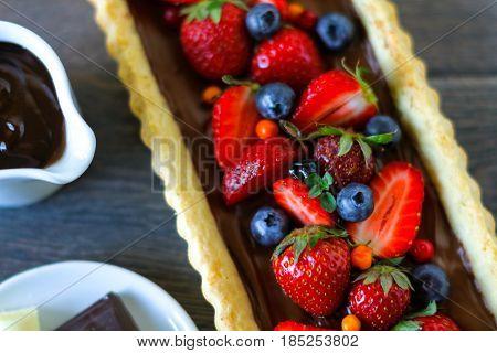Gourmet chocolate ganache tart with fresh strawberries and blueberries