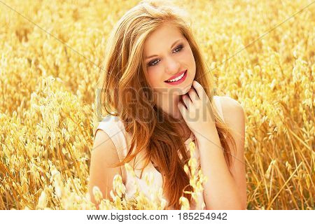 Carefree Adolescence. Portrait Of Attractive Young Red Haired Girl Dressed In White Dress Touching H