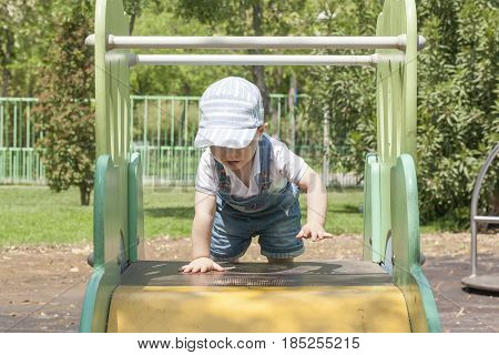 2 year-old boy reaching to the top of slider at playground. Tenacity concept