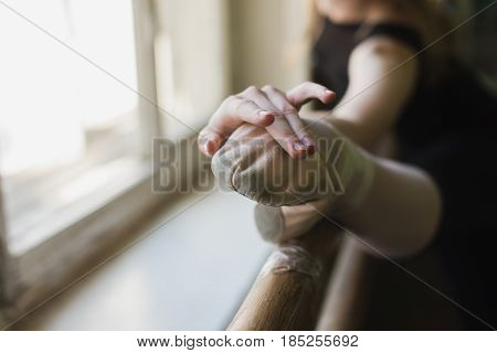 Young beautiful ballerina warming up in ballet class. Close up girl in black leotard stretch at ballet class stretching muscles at the barre. Focus on the leg
