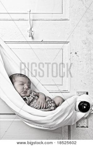 newborn baby sleeping in sling hung from door