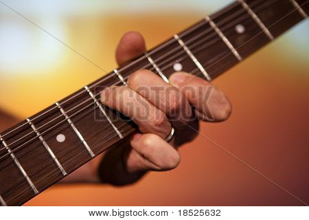 guitar players fingers playing chord
