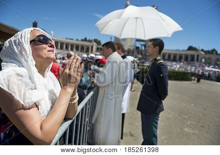 Fatima Portugal - May 13 2014: Woman praying at the Sanctuary of Fatima during the celebrations of the apparition of the Virgin Mary in Fatima Portugal.