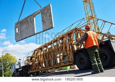 Construction industrial worker operating hoisting process of concrete slab