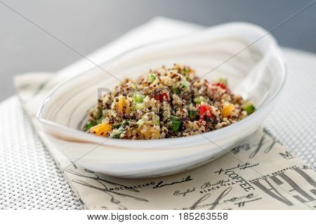 Quinoa salad bowl on white mat. Quinoa salads are very healthy and easy to do! Quinoa is a grain that originate from South America it's often called a super food due to its high nutritional content.
