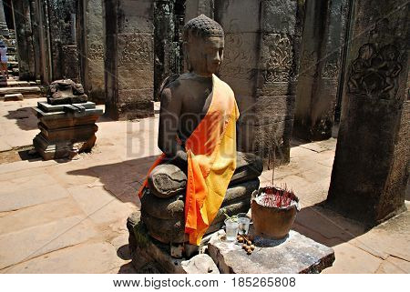 Buddhist statue in Ankor Wat. Incense and faith. Cambodia