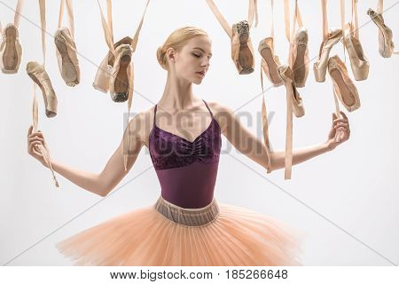 Charming ballerina with closed eyes in a violet top and a peach tutu stands on the light background in the studio. Around her there are many hanging beige pointe shoes. She holds ribbons of the shoes.