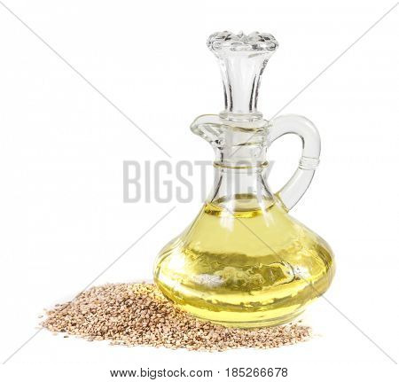 Jug with sesame oil and sesame seeds on white background