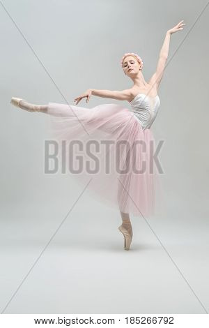 Elegant ballerina stands on pointe on the gray background in the studio. She wears a dance wear with white top and a rose skirt and has a wreath on her head. Her right leg is outstretched to the side.