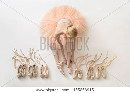 Nice ballerina sits on the white floor and dresses a beige pointe shoe in the studio. She wears a light dance wear and a peach tutu. On the sides there are ballet shoes. Top view photo. Horizontal.