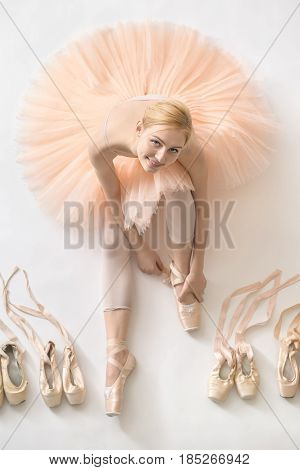 Happy ballerina sits on the white floor and looks into the camera in the studio. She wears a light dance wear and a peach tutu. On the sides there are ballet shoes. Top view photo. Vertical.