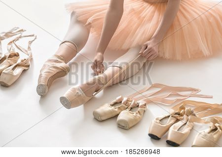 Girl who is ballerina sits on the white floor and dresses a beige pointe shoe in the studio. She wears a light dance wear and a peach tutu. On the sides there are ballet shoes. Closeup. Horizontal.