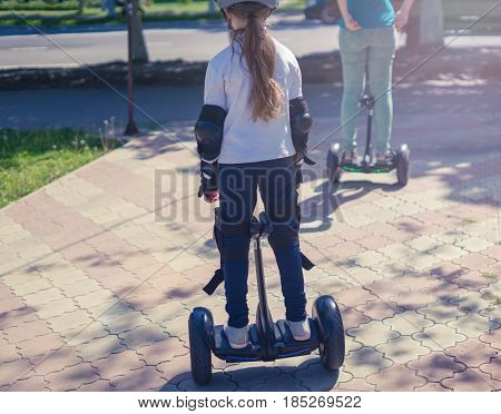 Young mother and daughter riding electric mini hoverboard in park. Family concept. Riding together.