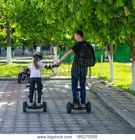 Young father and daughter riding electric mini hoverboard in park. Family concept. They are holding hands