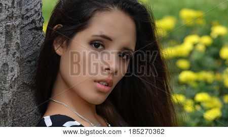 Confused Teen Girl Sitting in a Flower Meadow