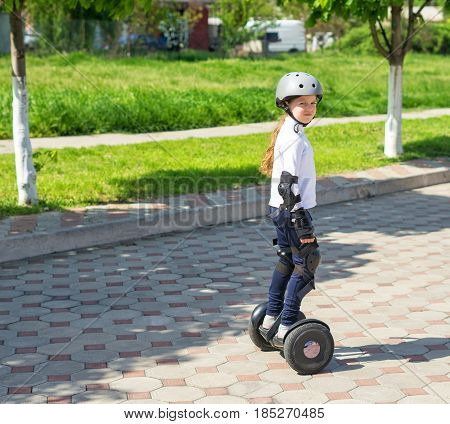 Small girl learns to ride electric mini hoverboard in the city. She is looking at the camera