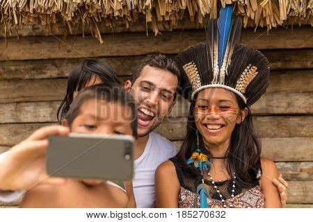 Tourist taking selfie photos with Native Brazilian from Tupi Guarani