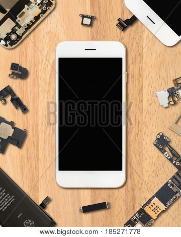 Flat Lay (Top view) of smartphone is surrounded by its own components on wooden background in 4:5 aspect ratio