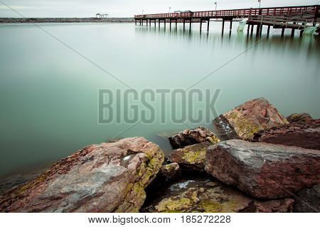 Exterior daytime long exposure winter picture of stones in foreground and green water of Lake Erie and dock in background in Buffalo, New York
