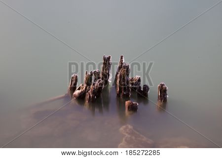 Exterior daytime long exposure stock photo of remnants of icy wooden pylons protruding from Lake Erie in Buffalo, New York in Erie County.