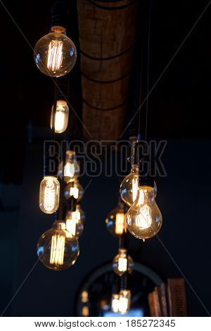 Shallow depth of field vintage electric light bulbs in the foreground with wooden slats in the background in dark dimly lit Western New York brew pub.