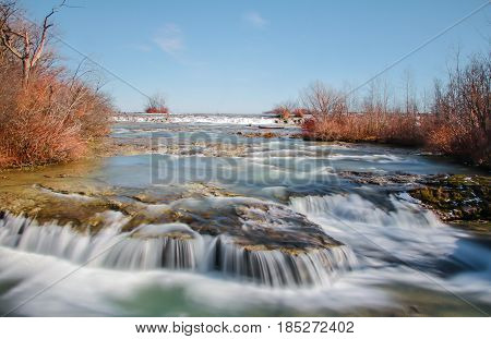 Long exposure exterior daytime stock photo of mini waterfall on Goat Island at Niagara Falls with blue sky background.