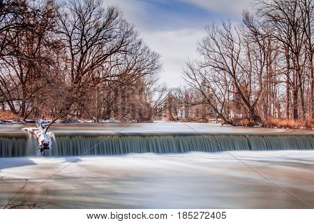 Long exposure exterior daytime stock photo of waterfall and felled log with blue sky background in Batavia, New York in Genesee County