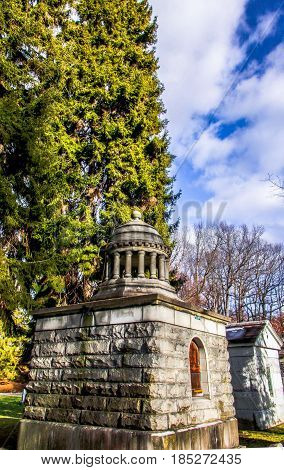 Exterior daytime stock photo of crypt in Mount Hope Cemetery in Rochester, York with cloudy blue sky in background.