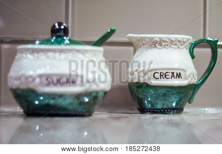 Shallow depth of field Irish creamer container on brown and white granite kitchen countertop with Irish sugar container in the foreground backed by clear tile backsplash