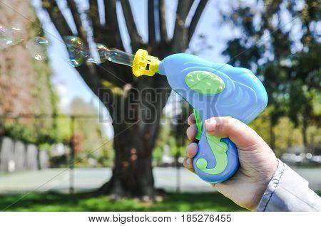 May 10 2017-Kid hand holding a bubbles gun and play at Memorial Park Vancouver,BC Canada