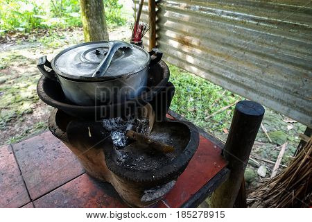 Thai stove, cooking tool. Traditional charcoal burning clay stove in a rustic wooden house
