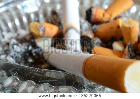 A close up image of a dirty ashtray with two lit cigarettes.