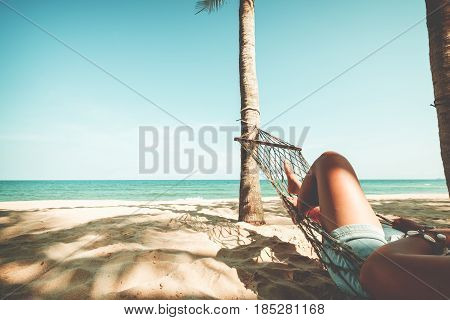 Leisure in summer - Beautiful Tanned legs of sexy women. relax on hammock at sandy tropical beach. vintage color styles