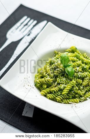 Basil pesto pasta vertical. Rotini pasta with basil pesto sauce grated parmesan cheese and fresh pepper. This Italian dish makes a delicious meal by itself or can be used as a pasta salad side.