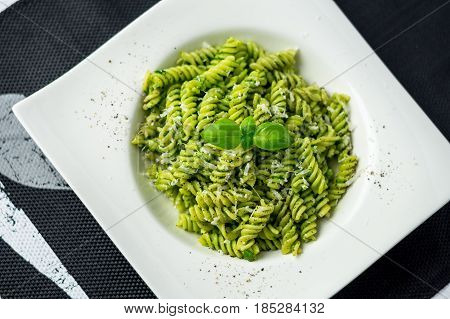 Rotini pesto pasta top view. Rotini pasta with basil pesto sauce grated parmesan cheese and fresh pepper. This Italian dish makes a delicious meal by itself or can be used as a pasta salad side.