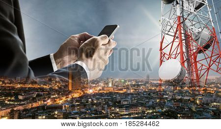 Businessman using smartphone with double exposure modern cityscape in sunrise, and telecommunication towers