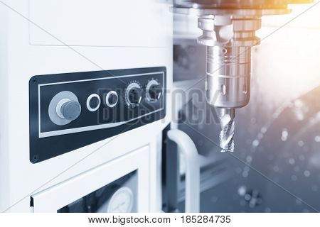 The CNC milling machine with the controller panel in light blue scene .The rough end mill cutter for CNC machine with lighting effect