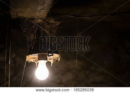 Glowing lamp in a dirty barn. Old web